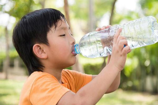 Bé trai bổ sung thêm nước sau khi hoạt động thể chất